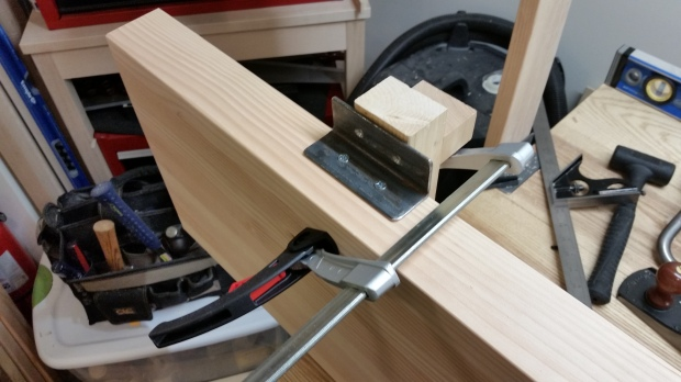 My shop-made sharpening depth stop block makes a great backerboard for installing angle irons.